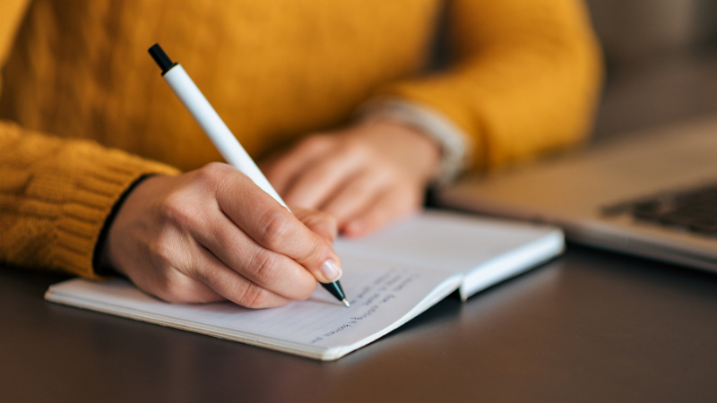A person writing on a piece of paper  Description automatically generated with medium confidence