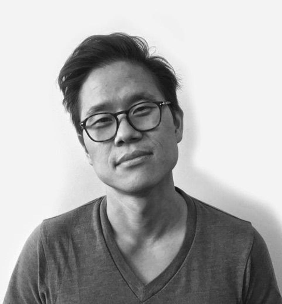 An Asian man with glasses in a black and white photo.