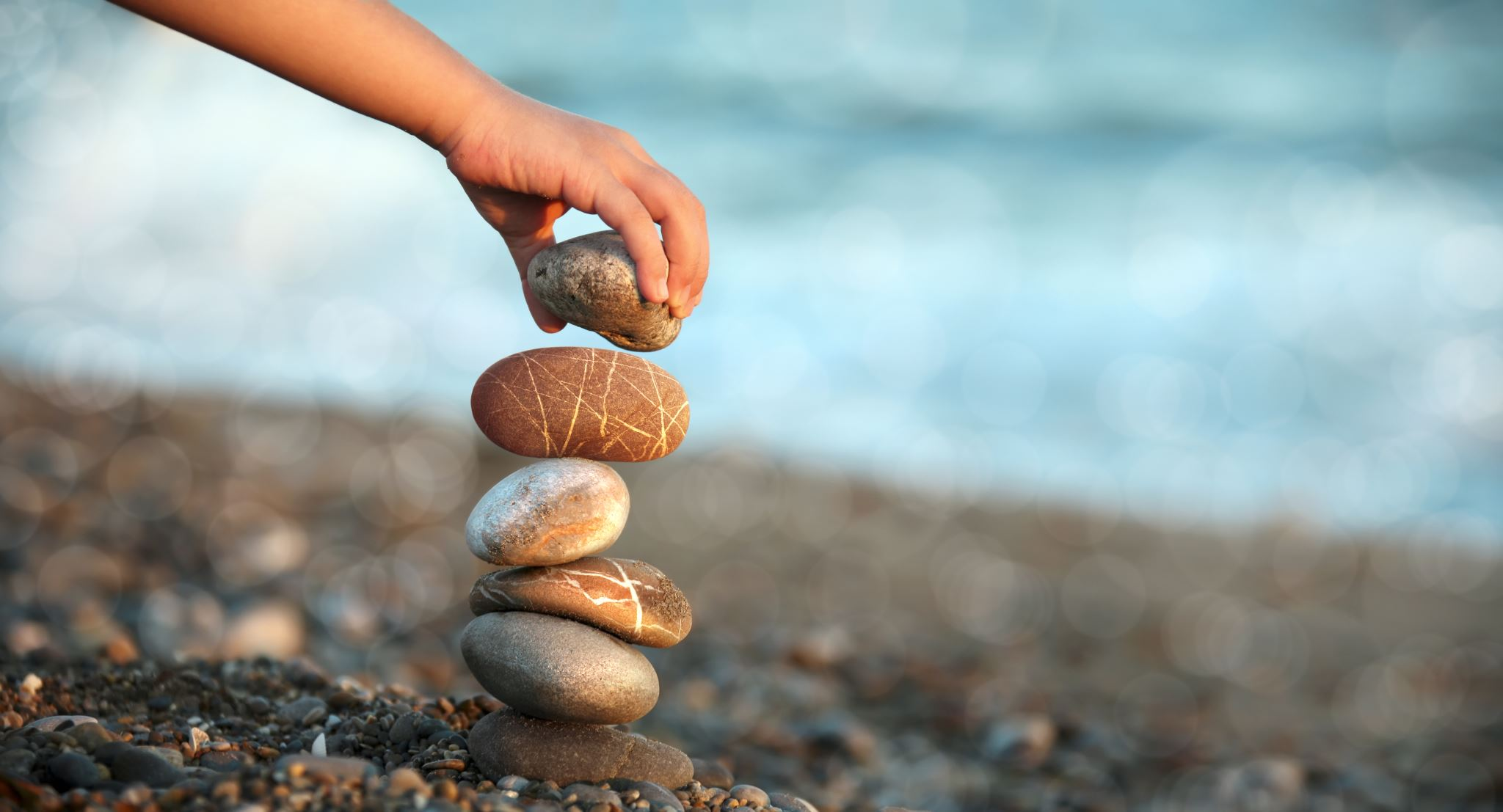 Child stacking rocks on a beach