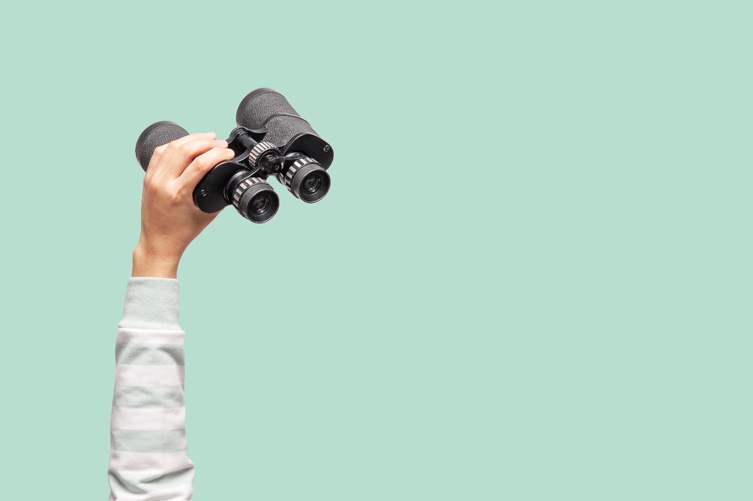 Hand holding binoculars