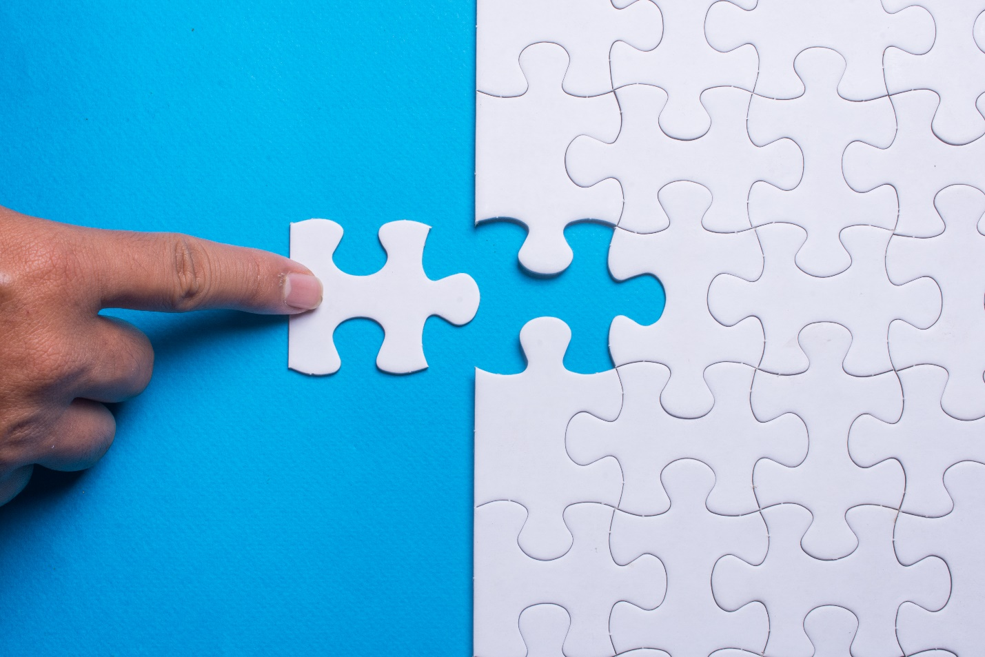 Hand holding piece of white puzzle on blue background