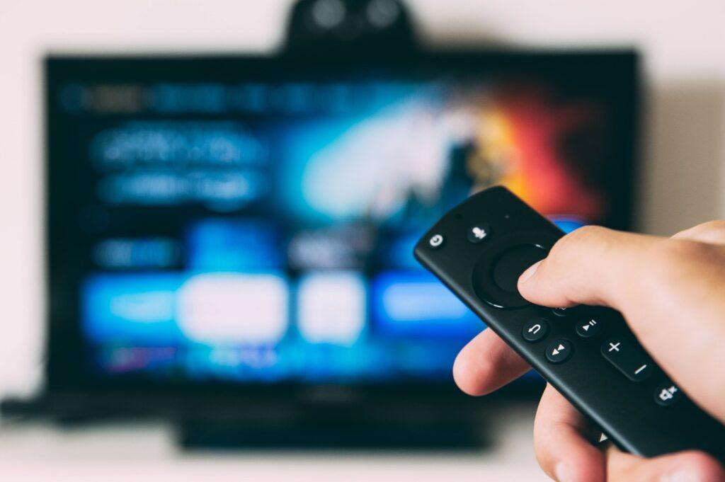 hình ảnh bàn tay điều khiển điều khiển từ xa chỉ vào tivi