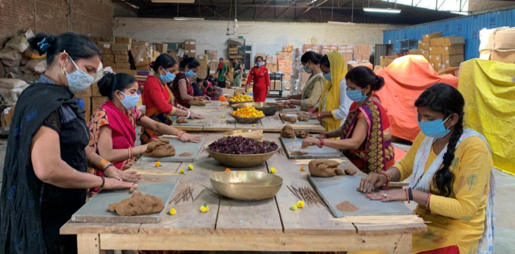 Hình ảnh những người thợ làm nhang dùng bột từ những bông hoa bỏ đi bên ngoài đền thờ