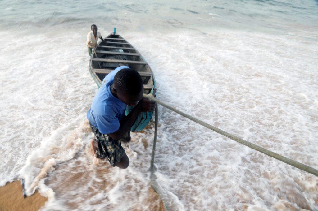 Những người đàn ông kéo thuyền từ biển vào bờ biển ở làng chài Port Bouet ở Abidjan, Bờ Biển Ngà ngày 12 tháng 2 năm 2021.