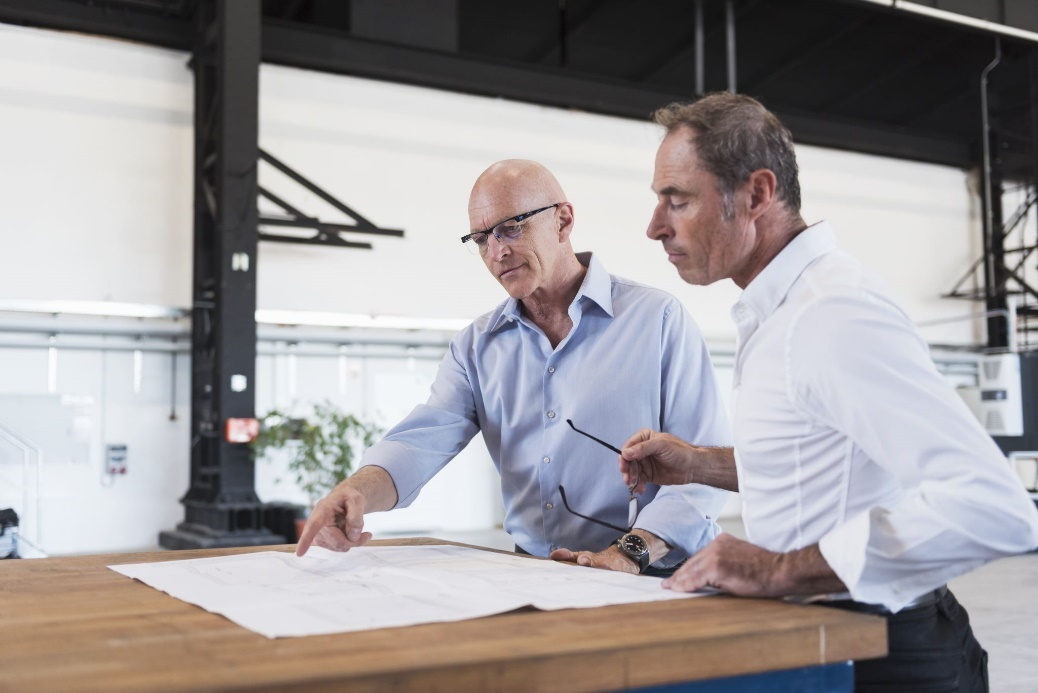 Two businessmen looking at plan on table